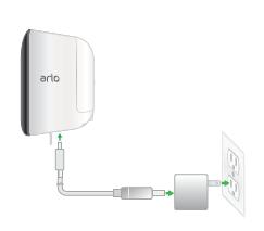 Ein Bild eines Arlo Security Light, das an das USB-Ladekabel angeschlossen ist, das an das Netzteil angeschlossen ist, das an eine Steckdose im Innenraum angeschlossen ist